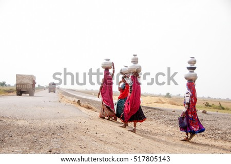 BHUJ, KUTCH, GUJARAT, 15 OCTOBER 2011 : Unidentified rural Indian women carry water on their heads in traditional pots from well, everyday Women walk few kilometers to get water due to drought.
