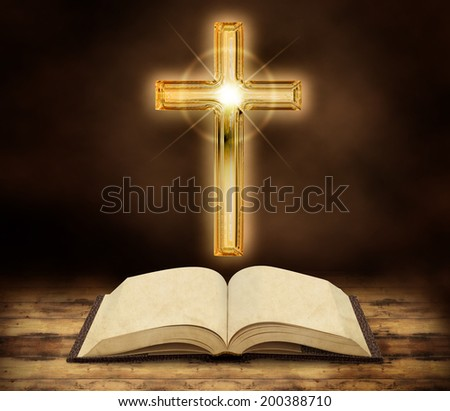 bible and glowing crucifix on dark wooden background - stock photo