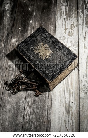 bible and keys a german antik bible with a bunch of keys laying on a wooden table - stock photo