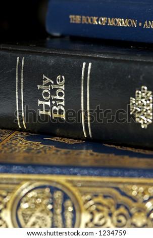 Bible and Koran (Qur'an) and Book of Mormon (focus on Bible) - stock photo