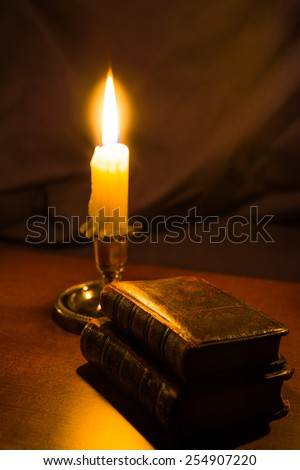 Bible and old books and candle on a wooden table. Focus on the old books