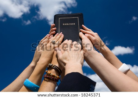 Bible in hand on background blue sky - stock photo