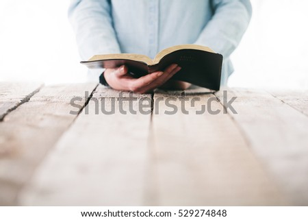Bible in hands of a woman. She is reading and praying over it
