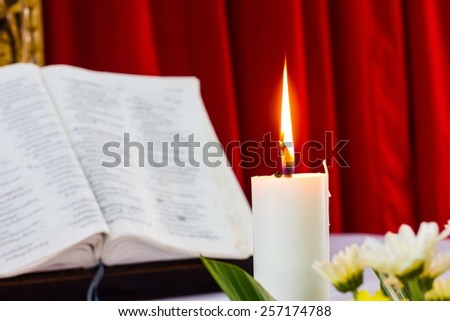 bible open on a table with candle and red curtain as background. flower as foreground. Perfect for religion, easter and christmas themes. candle fucused - stock photo