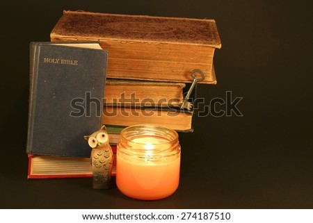 Bible with a stack of old books, a candle, key and an owl on a black background - stock photo