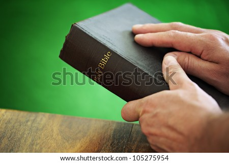 Bible with mans hand resting on the cover whilst holding in front of a green background - stock photo