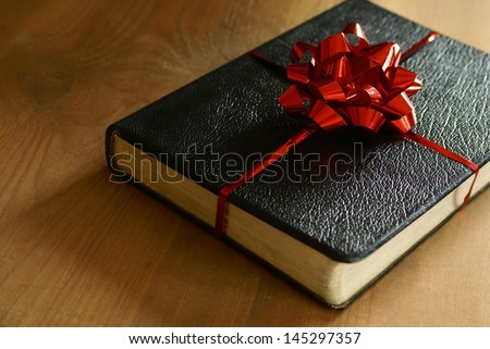 Bible with ribbon as a gift on wooden background.