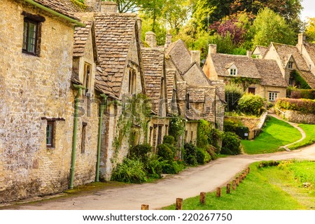 BIBURY, ENGLAND, UK - SEPTEMBER 21, 2014: Arlington Row traditional Cotswold stone cottages in Gloucestershire on September 21, 2014, England. Bibury it the most depicted village in the world.