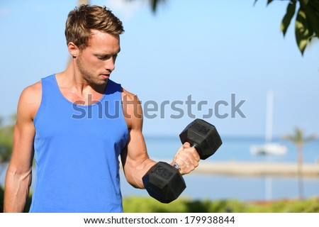 Bicep curl - weight training fitness man outside working out arms lifting dumbbells doing biceps curls. Male sports model exercising outdoors as part of healthy lifestyle. - stock photo