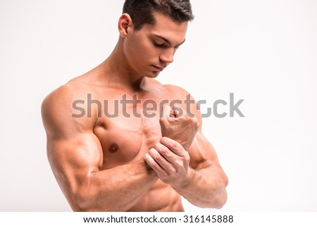 Biceps and pecs muscle of a young athletic man, isolated on white background. - stock photo