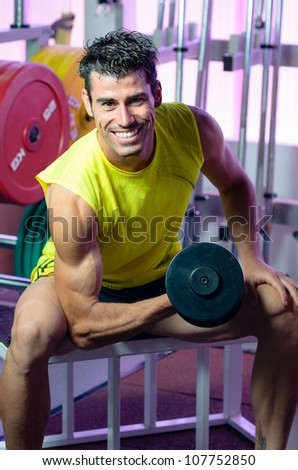 Biceps exercise with weights in Gym. Fit sportsman training arms and looking at camera. - stock photo