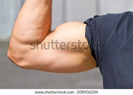Biceps of athletic man - stock photo