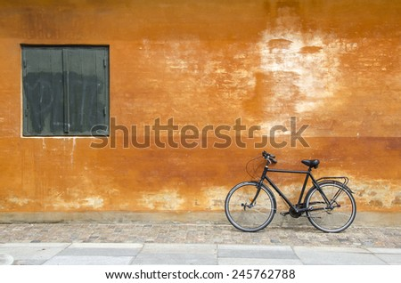 Bicycle against bright wall in Copenhagen - stock photo