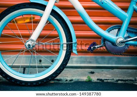 Bicycle against orange metal door. Urban modern concept - stock photo