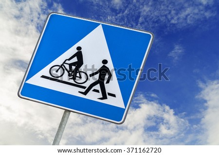 Bicycle and pedestrian road sign on blue sky, bike cycling and walking - stock photo