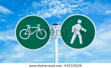 Bicycle and pedestrian shared route sign on cloudy sky background - stock photo