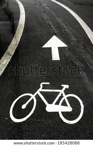 Bicycle asphalt lane, with white bike symbol and arrow symbol. - stock photo