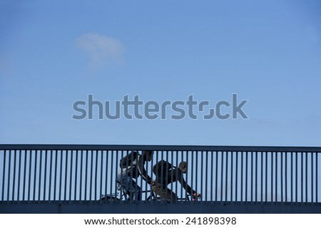 Bicycle Commuters on a Railing of bridge - stock photo