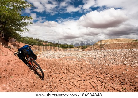 bicycle costs on drought stricken landscape of cracking earth surface - concept image of global warming. Background blue sky, green hills, clouds. - stock photo