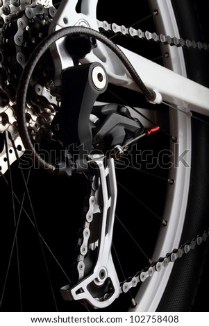 Bicycle gears and rear derailleur. Studio shot on black background.