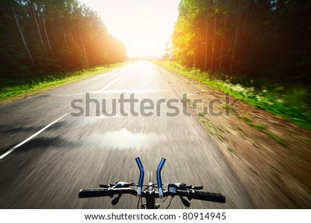 Bicycle handlebar and motion blurred asphalt road through a forest - stock photo