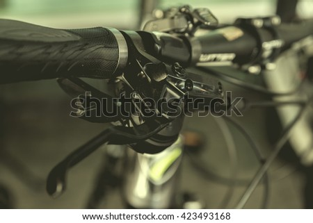 Bicycle handlebar close up, brake in focus with vignette