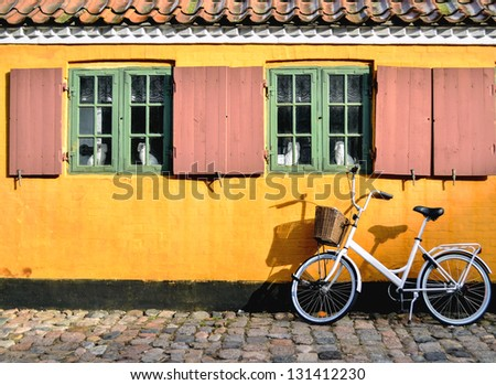 Bicycle in front of the entrance to an apartment in one of the houses named Nyboder - stock photo