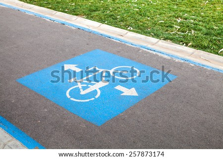 Bicycle lane. Blue and white road marking over urban asphalt road and green grass  - stock photo