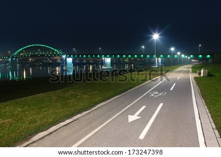 Bicycle lane with white bicycle sign at night - stock photo