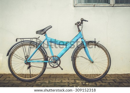 bicycle leaning against an old plaster wall home - stock photo