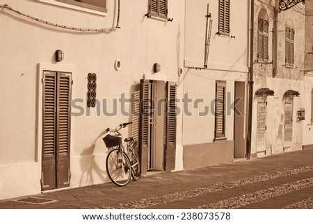 bicycle leaning against the wall in Alghero. Processed for sepia effect. - stock photo