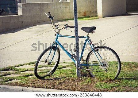Bicycle left abandoned locked to a metal pole. - stock photo