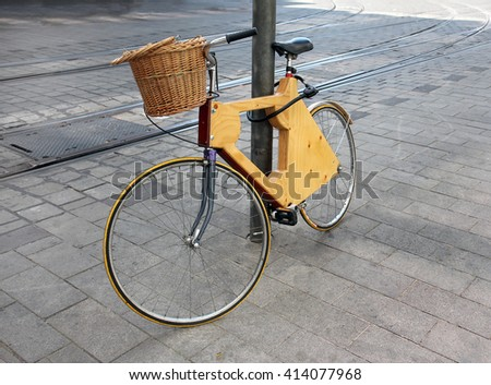 Bicycle made of wood stands near a column - stock photo