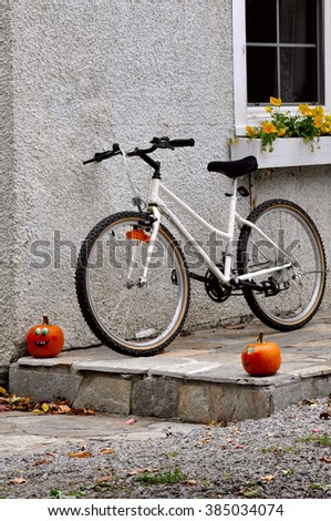 Bicycle near house wall with halloween decoration. - stock photo