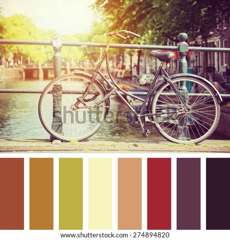 Bicycle on a bridge in sunlight, Amsterdam. In a colour palette with complimentary colour swatches. - stock photo