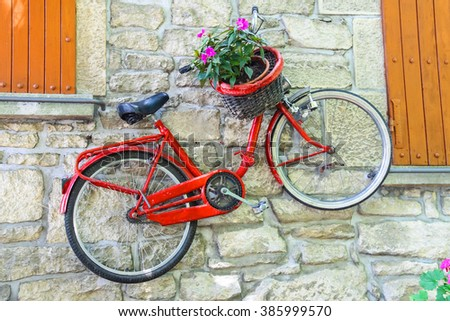Bicycle on a wall with flowers in a basket - stock photo
