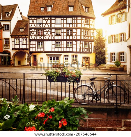 Bicycle on cobblestone street with half timbered houses in Colmar old city, Alsace, France. Toned in warm colors.  - stock photo