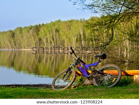 Bicycle on the bank of a beautiful forest lake - stock photo