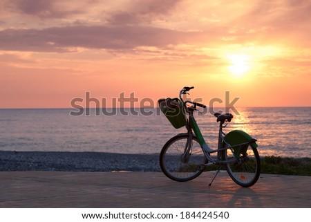 Bicycle on the pavement on Batumi beach, sunset - stock photo
