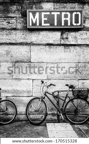 Bicycle parked against a stone block wall under a French metro subway sign. Black and white image. Copy space. - stock photo