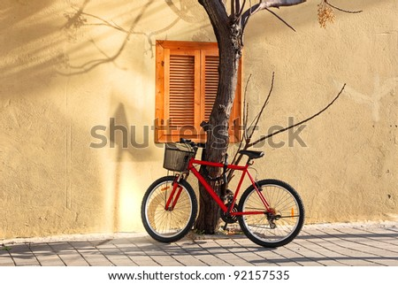 Bicycle parked near a tree on the house wall background on sunny winter day - stock photo