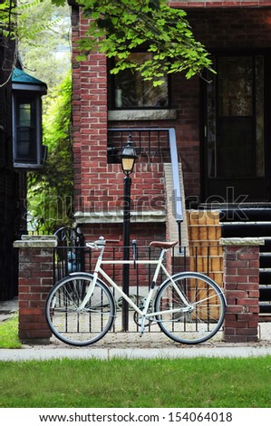 Bicycle parked near steel fence on the street in Toronto - stock photo
