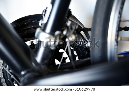 Bicycle parts with narrow depth of field. This picture highlights the front sprocket and chain, with the frame in the foreground slightly blurred. Color and white balance are cooled slightly.