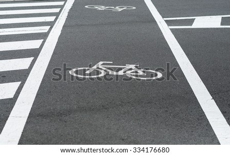 Bicycle path lane with white bicycle symbol on asphalt road