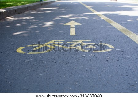 Bicycle path sign on the street. Photo was taken on a nice sunny day. Summer time. Focus is on the middle of the sign. On the side is road shoulder.  - stock photo