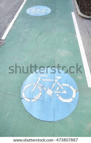 Bicycle path signs on a green painted road.