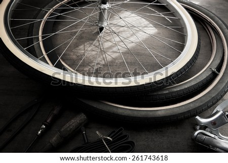 Bicycle repair in monotone. Repairing or changing a tire, tire tubes and brakes wires of an vintage bicycle. - stock photo