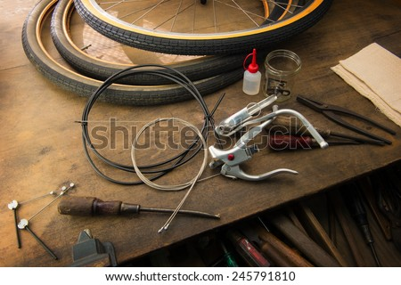 Bicycle repair. Repairing or changing a tire, brakes etc of an vintage bicycle. Old bicycle wheels on a grungy work desk with well used tools and bicycle parts.  - stock photo