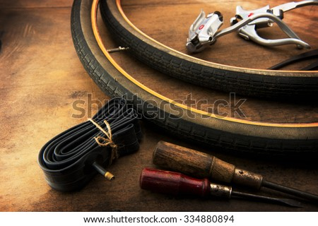 Bicycle repair. Repairing or changing a tire or wheel of an bicycle. Old bicycle wheels on a grungy work desk with inner tube and well used tools and bicycle parts.  - stock photo