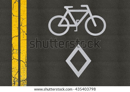 Bicycle reserved road sign on asphalt with double yellow lines - stock photo